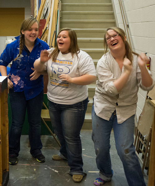 Theater students Haley Tripp, left, Cheney Peterson, and Carson Holwell dance to the music during a break from painting on the stage set of 'Grease' Saturday, Jan. 25, 2014 at Sheridan High School.