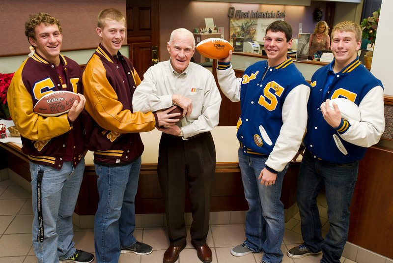 From left, Big Horn Rams Running back Colter Carzoli and Quarterback Connor McCafferty pose with Homer Scott, Jr. and Sheridan Broncs Running Back Danniel Sessions and Linebacker Ethan Hall on Wednesday, Nov., 27, 2013, at the First Interstate Bank on Main Street. (The Sheridan Press/Justin Sheely)
