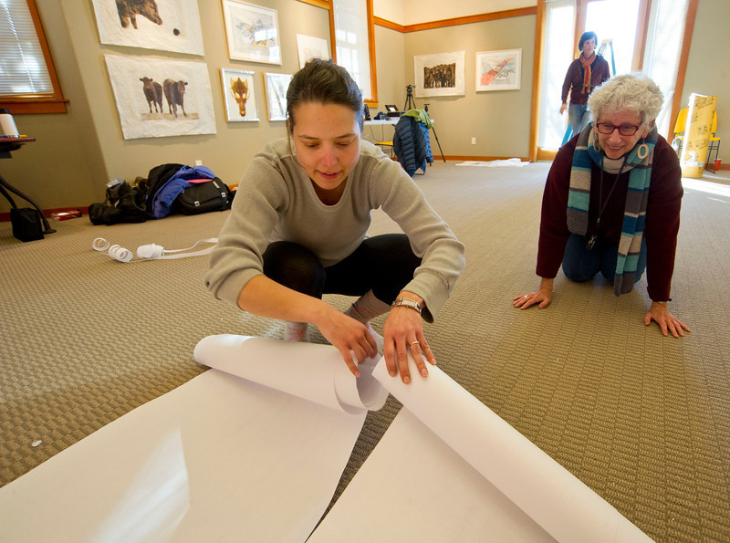 "Kristina Arnold, left, and Susan Hillyard roll up the long sheets of paper that will be the centerpiece of ""The Beast"" project Tuesday at the Sheridan Community Art Center in the Historic Train Depot. The Beast is a collaborative effort from five former Jentel Foundation residents to interpret what 'beast' means and how it should be expressed."