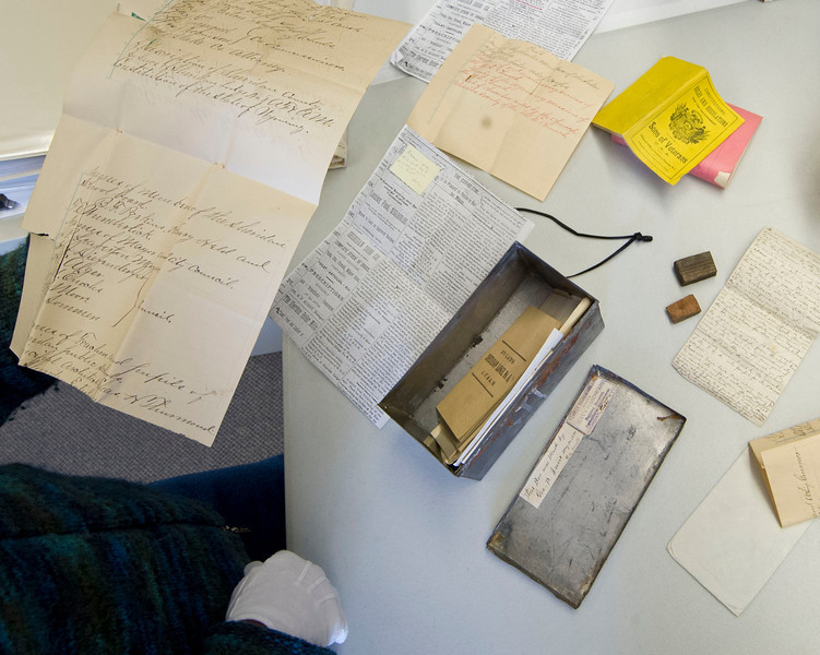 Slack spreads out the contents of the time capsule on a table in THE Wyoming Room Tuesday at the Sheridan County Fulmer Public Library.