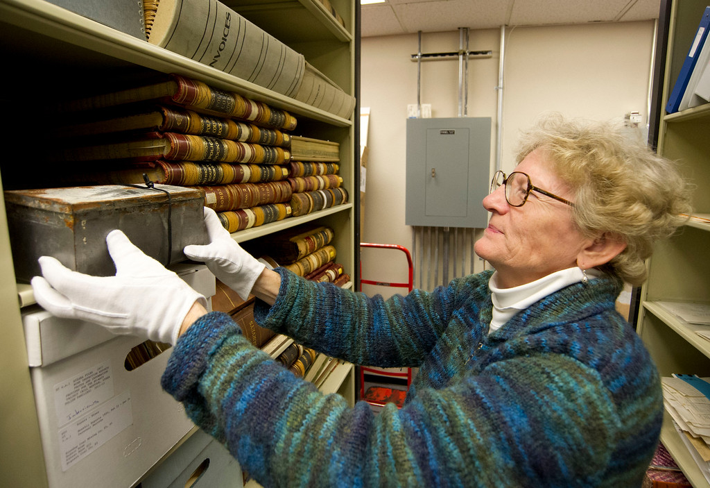 Director of THE Wyoming Room Judy Slack pulls the time capsule box from a shelf in the storage area Tuesday at the Sheridan County Fulmer Library.