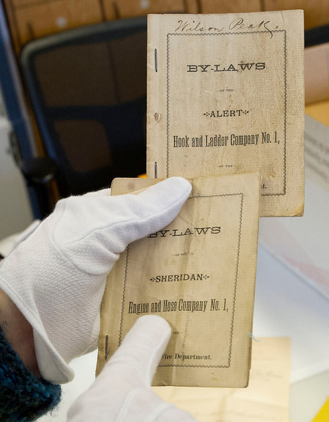 Slack pulls out two Bylaws handbooks from the Sheridan Hook and Ladder Company and the Sheridan Engine and Hose Company in THE Wyoming Room Tuesday at the Sheridan County Fulmer Public Library.