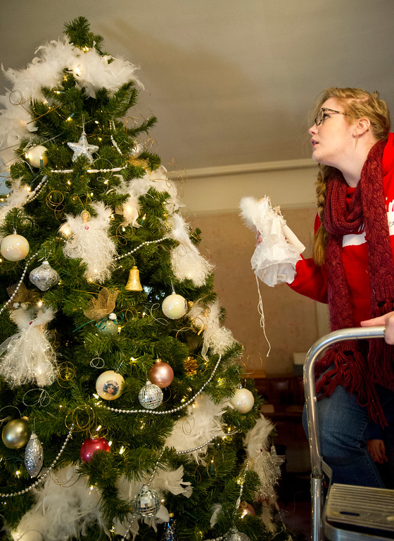 Micah Cornell moves up a stepladder to place an angel tree-topper on a Christmas Tree in the master bedroom of the Trail End Museum at Kendrick Mansion on Saturday. The Trail End's annual Holiday Open House will be held this December 6 – 8, from 4p.m. – 7p.m.