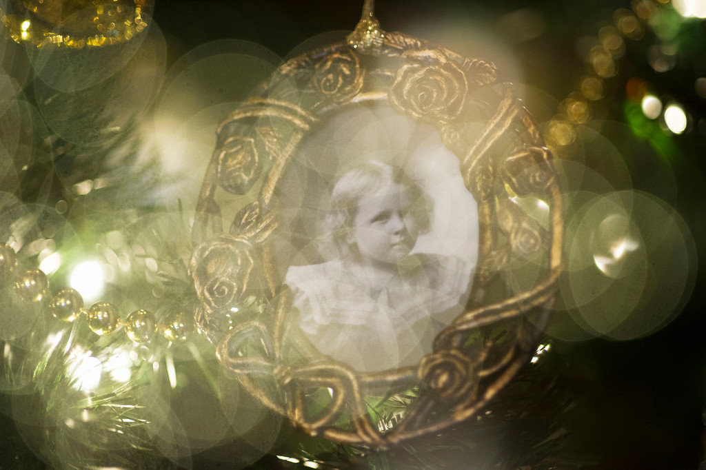 A child's portrait is hung as an ornament on a Christmas tree in the main lobby of the Trail End museum.