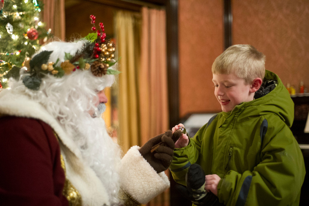 7-year-old Judge Fleck accepts a reindeer bell from Father Christmas Friday night during the Trail End Holiday Open House at Kendrick Mansion.