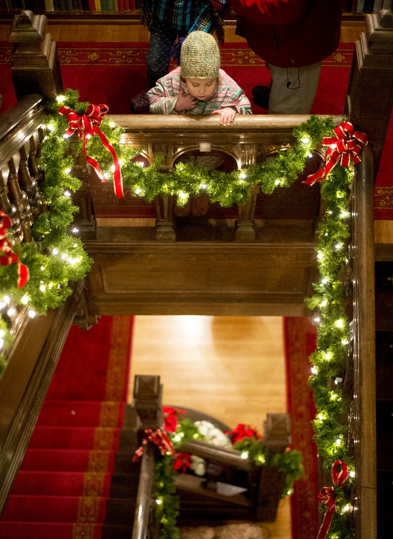 Ali Tellez, 3, looks over the stair rail Friday night during the Trail End Holiday Open House at Kendrick Mansion.