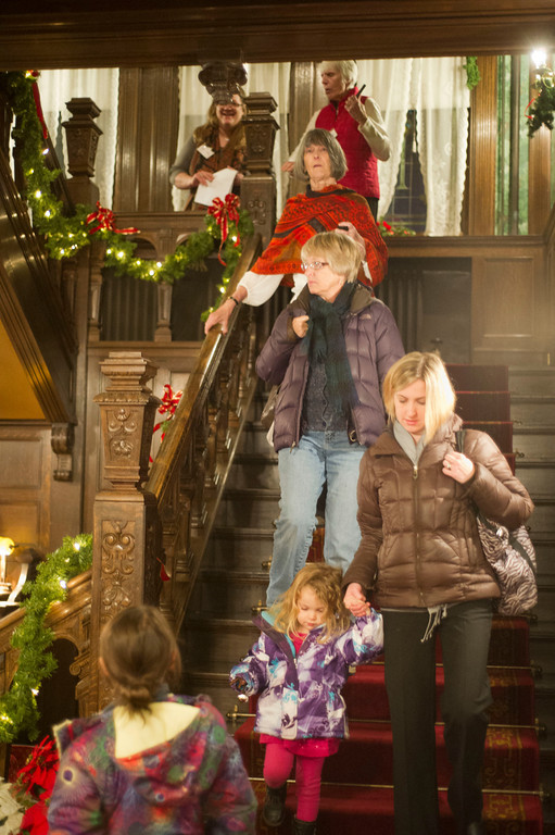 Guests decend the main stair way Friday night during the Trail End Holiday Open House at Kendrick Mansion.
