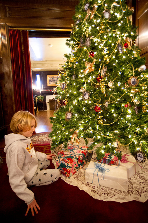 8-year-old Myra Fuhrman takes a moment to gaze at the Christmas tree after placing wrapped boxes underneath on Saturday at the Kendrick Manson Trail End museum.