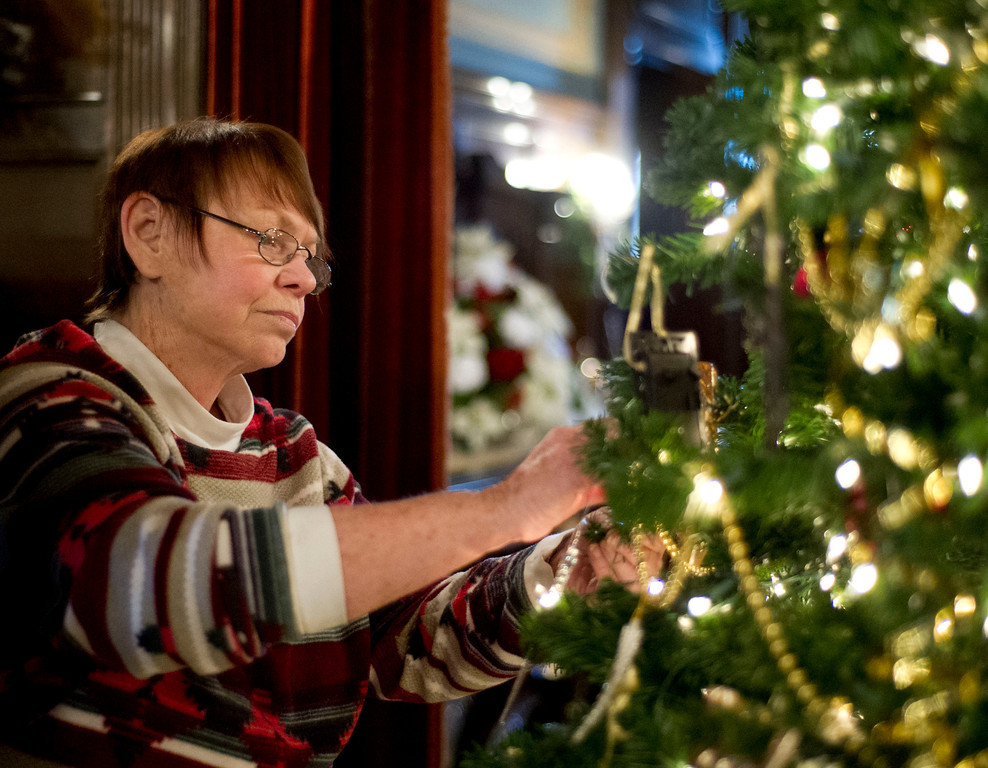 Volunteer Patti Roth hangs an ornament on the Christmas tree in the main lobby at Kendrick Mansion on Saturday. Several volunteers help the Trail End museum prepare every year to the annual Holiday Open House.