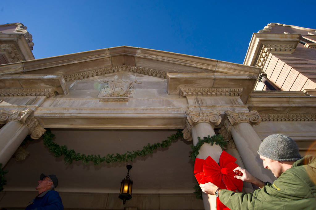 Volunteer Ryan Fuhrman adjusts a large red bow on one of the pillars of the main entrance to Kendrick Mansion on Saturday.
