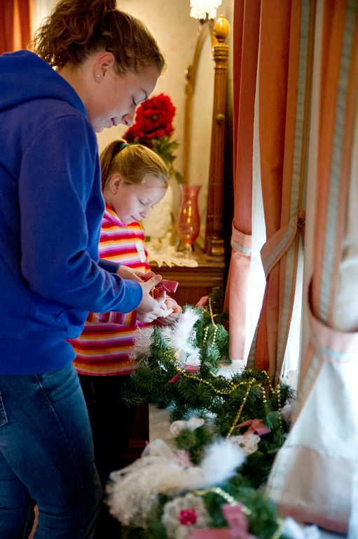 Volunteers Gabbie Moore, left, and her 8-year-old sister Gracie Moore decorate the window of the Master Bedroom at Kendrick Mansion on Saturday.