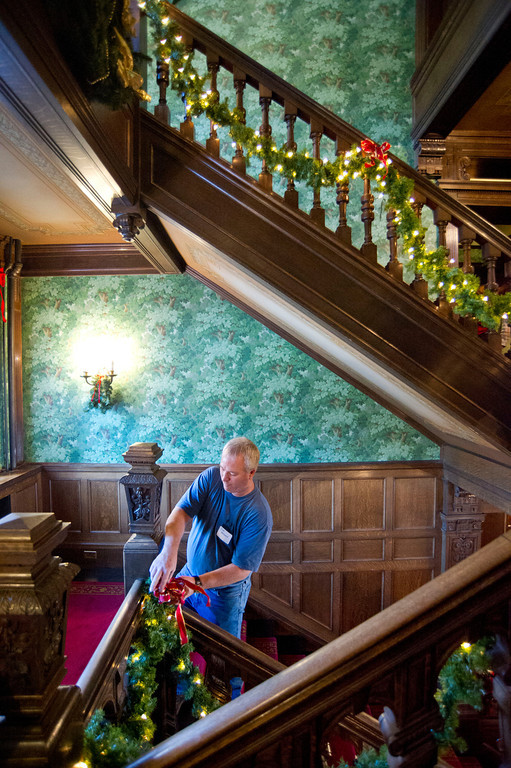 Bob Aksamit ties a bow to the garland along the stairway railing Saturday at Kendrick Mansion.