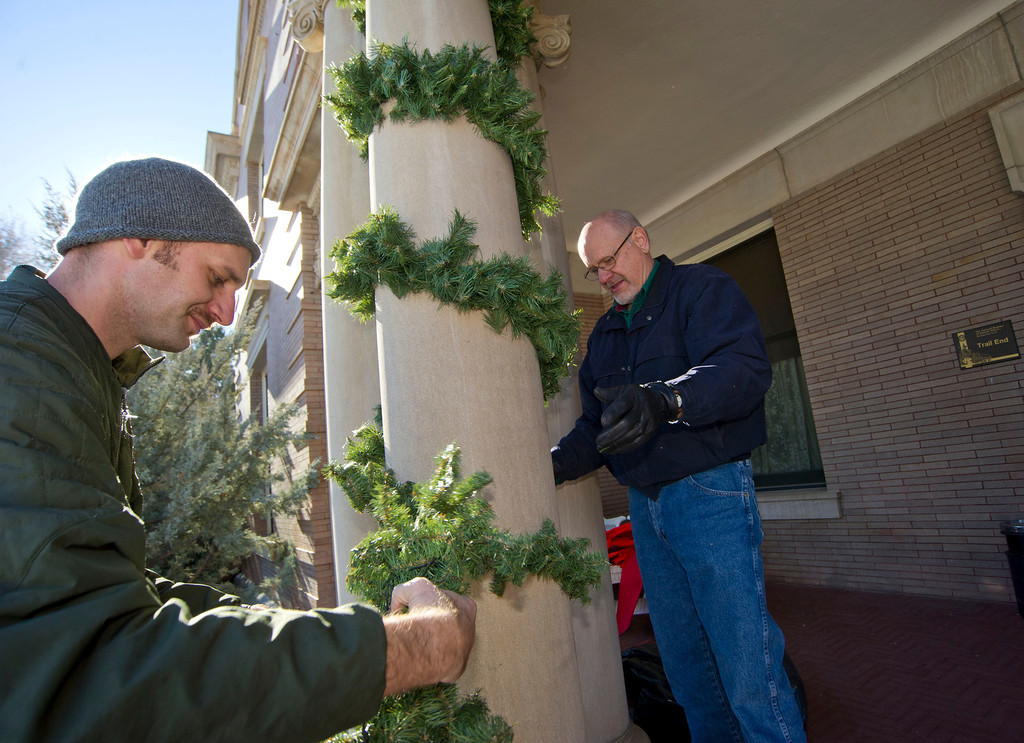 Ryan Fuhrman, left, wraps Christmas décor around a pillar with Roger Fuhrman at the main entrance to the Trail End Museum at Kendrick Mansion on Saturday. The Trail End's annual Holiday Open House will be held this December 6 – 8, from 4p.m. – 7p.m.