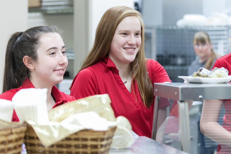 Tibby McDowell | The Sheridan Press<br /> Jenna Keller, left, and Emma Schroder serve dinner to attendees prior to the production of Beauty and the Beast at Tongue River High School Auditorium Tuesday, March 6, 2018.