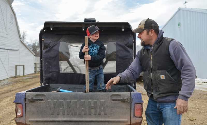 Justin Sheely | The Sheridan Press<br /> Levi Gorzalka walks around a side-by-side vehicle with his son Tallis Gorzalka, 4, at the Bow & Arrow Ranch west of Sheridan Thursday, March 15, 2018. March is a critical time of year for area ranchers as they work around the clock to ensure the survival and health of newborn calves.
