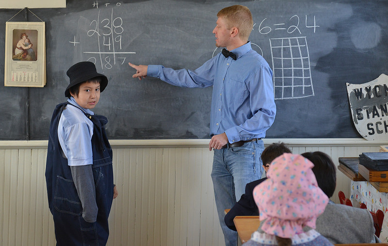 Justin Sheely | The Sheridan Press<br /> Second-grader Zion Bright Wing looks back as teacher Jesse Hinkhouse instructs him on a math problem during a historic social studies class at the Owen School in Ranchester Tuesday, April 10, 2018. Tongue River and Big Horn elementary students experienced the teaching and disciplinary methods of the classroom of 100 years ago in the historic one-room schoolhouse.