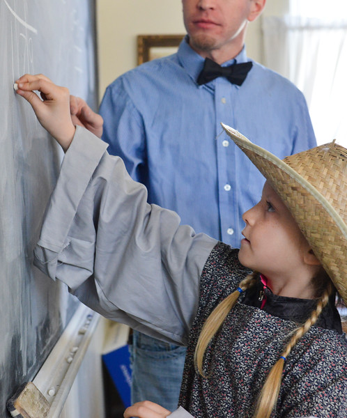 Justin Sheely | The Sheridan Press<br /> Tongue River second-grader Leah Melger writes on the chalkboard during a historic social studies class at the Owen School in Ranchester Tuesday, April 10, 2018. Tongue River and Big Horn elementary students experienced the teaching and disciplinary methods of the classroom of 100 years ago in the historic one-room schoolhouse.