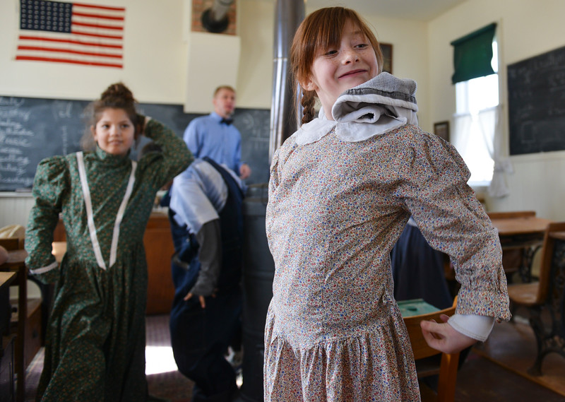 Justin Sheely | The Sheridan Press<br /> Tongue River student Haley Barker takes off her costume as the students break for recess during a historic social studies class at the Owen School in Ranchester Tuesday, April 10, 2018. Tongue River and Big Horn elementary students experienced the teaching and disciplinary methods of the classroom of 100 years ago in the historic one-room schoolhouse.