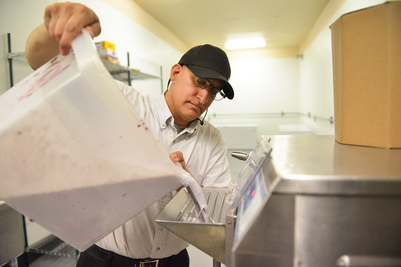 Justin Sheely | The Sheridan Press<br /> Business owner Louis Mitchell pours a mixture for blueberry ice cream into a batch freezer at the Cowboy Creamery on North Main Street Tuesday, June 5, 2018.