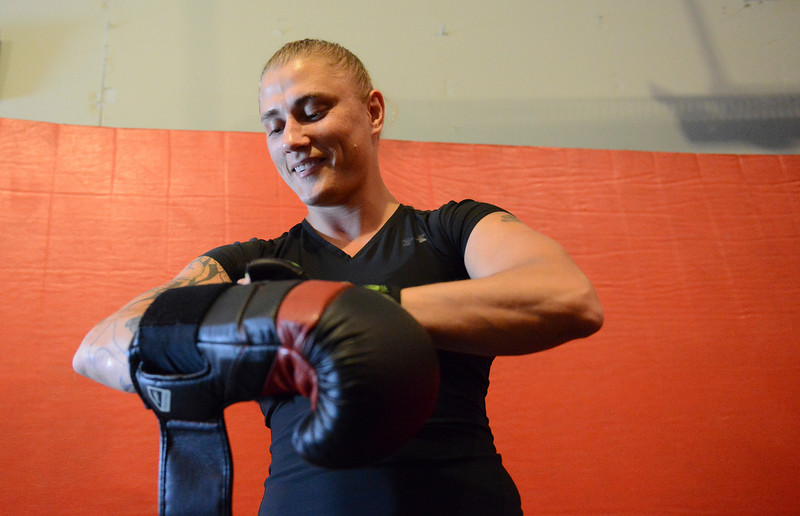 Justin Sheely | The Sheridan Press<br /> Amature MMA fighter Nekah Dmitriyeva straps on sparring gloves at coach Valdez's home Tuesday, June 5, 2018. Dmitriyeva and her coach are hoping to go pro after a MMA championship in Denver, Colorado, at the end of June.