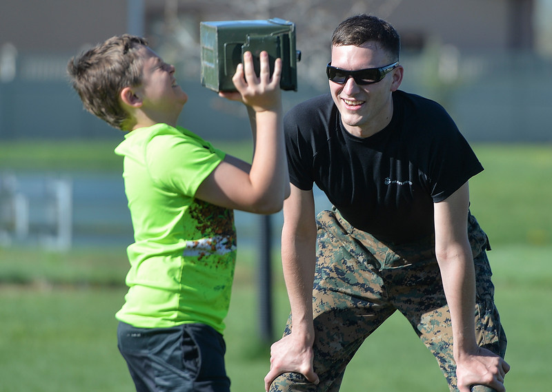 Justin Sheely | The Sheridan Press<br /> Sgt. Justin Dommer counts as Fourth-grader Jake Harmon lifts a 15-pound ammo box over his head for a Marine combat fitness test at Woodland Park Elementary School Wednesday, May 16, 2018. SCSD2 health and physical education teacher Jessica Pickett brought the test to schools after attending a Marine Educator Workshop in April. Pickett believes educators can incorporate other lessons about teamwork and leadership from the Marines.