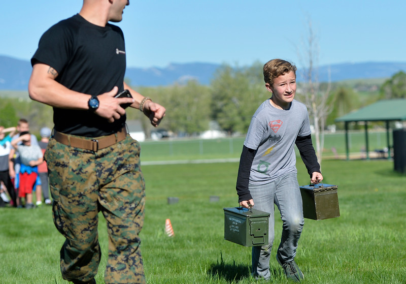 Justin Sheely | The Sheridan Press<br /> Fourth-grader Shaun Gonda carries ammo boxes as staff sgt. Cody Wallace runs with him during a Marine combat Fitness test at Woodland Park Elementary School Wednesday, May 16, 2018. SCSD2 health and physical education teacher Jessica Pickett brought the test to schools after attending a Marine Educator Workshop in April. Pickett believes educators can incorporate other lessons about teamwork and leadership from the Marines.