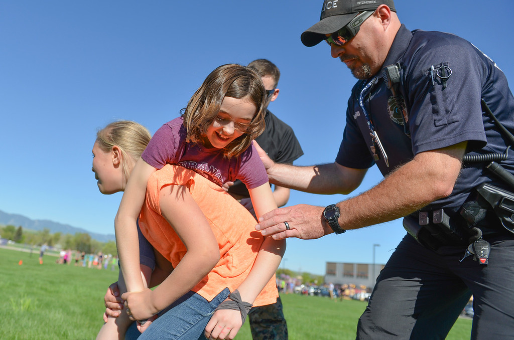 Justin Sheely | The Sheridan Press<br /> SRO Howie Fitzpatrick helps Fourth-grader Lexi Redinger lift Emmy Rambur in a fireman's carry for a Marine combat fitness test at Woodland Park Elementary School Wednesday, May 16, 2018.. SCSD2 health and physical education teacher Jessica Pickett brought the test to schools after attending a Marine Educator Workshop in April. Pickett believes educators can incorporate other lessons about teamwork and leadership from the Marines.