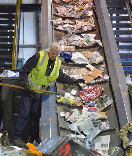 Justin Sheely | The Sheridan Press<br /> <br /> John Robert feeds material onto the sorting belt at the Sheridan Recycling Center Tuesday, Jan. 30, 2018. The city has seen a significant increase in recycled material along with a decrease in solid waste since they rolled out residential curbside recycling in 2015