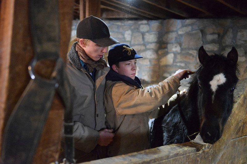 Justin Sheely   The Sheridan Press<br /> Arvada-Clearmont High School junior Tanner Klatt, left, and brother Cameron Klatt bring a foal in for feeding inside the barn at the Quarter-Circle 7 ranch near Arvada Friday, Dec. 22, 2017. The brothers live on a ranch in Campbell County, about 40-miles from their high school in Clearmont. Every day the brothers balance work on the ranch, school and playing on the Panthers basketball team.