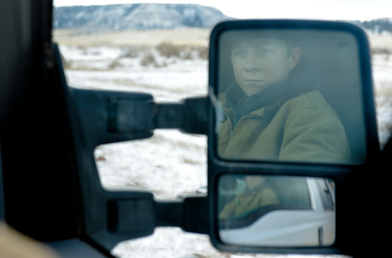 Justin Sheely   The Sheridan Press<br /> Arvada-Clearmont High School freshman Cameron Klatt looks out of the truck as the brothers ride out to feed the bulls at the Quarter-Circle 7 ranch near Arvada Friday, Dec. 22, 2017. The brothers live on a ranch in Campbell County, about 40-miles from their high school in Clearmont. Every day the brothers balance work on the ranch, school and playing on the Panthers basketball team.