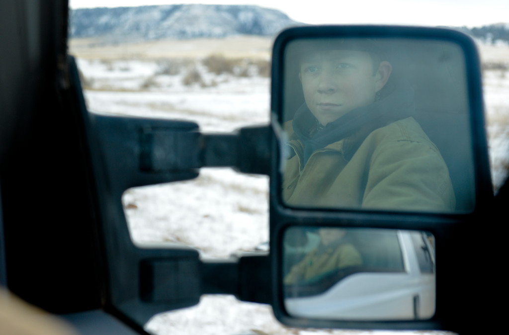 Justin Sheely | The Sheridan Press<br /> Arvada-Clearmont High School freshman Cameron Klatt looks out of the truck as the brothers ride out to feed the bulls at the Quarter-Circle 7 ranch near Arvada Friday, Dec. 22, 2017. The brothers live on a ranch in Campbell County, about 40-miles from their high school in Clearmont. Every day the brothers balance work on the ranch, school and playing on the Panthers basketball team.