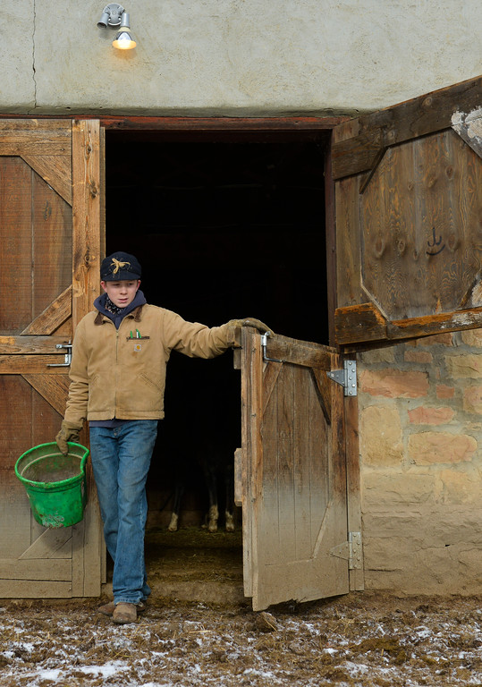 Justin Sheely | The Sheridan Press<br /> Arvada-Clearmont High School freshman Cameron Klatt feeds walks out of the barn to feed some calves at the Quarter-Circle 7 ranch near Arvada Friday, Dec. 22, 2017. The brothers live on a ranch in Campbell County, about 40-miles from their high school in Clearmont. Every day the brothers balance work on the ranch, school and playing on the Panthers basketball team.