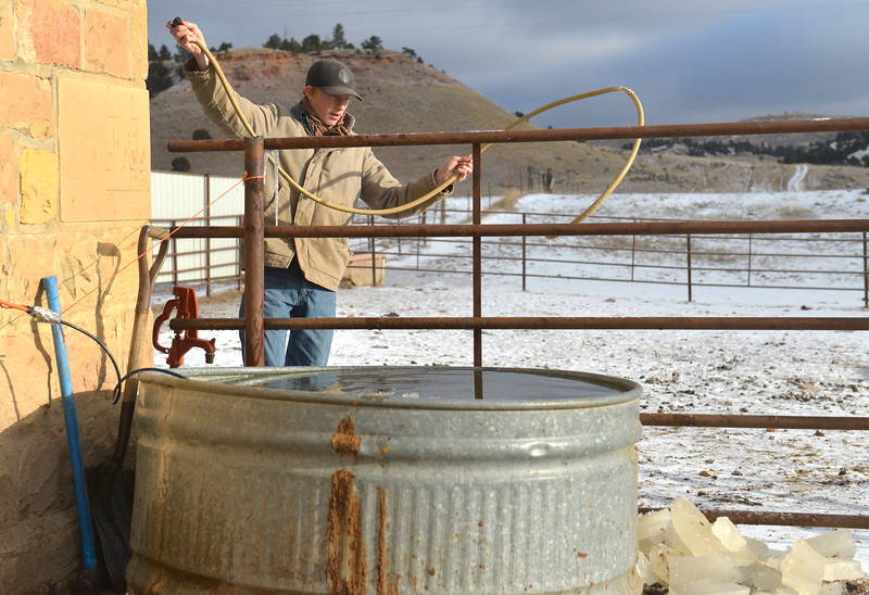 Justin Sheely   The Sheridan Press<br /> Arvada-Clearmont High School junior Tanner Klatt pulls a hose out of a water tank for their cows at the Quarter-Circle 7 ranch near Arvada Friday, Dec. 22, 2017. The brothers live on a ranch in Campbell County, about 40-miles from their high school in Clearmont. Every day the brothers balance work on the ranch, school and playing on the Panthers basketball team.