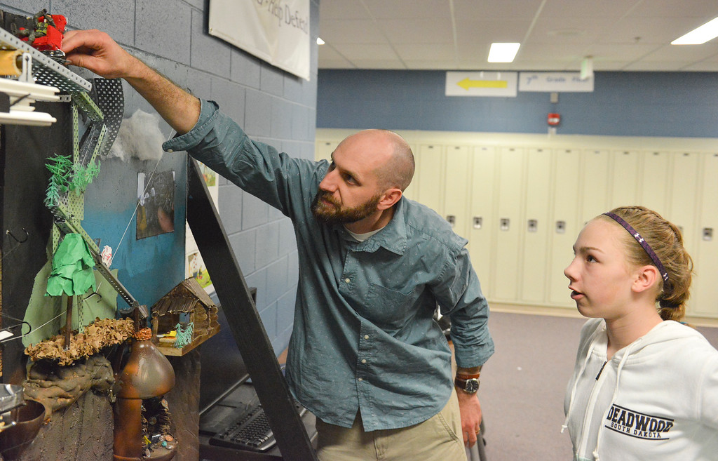 Justin Sheely | The Sheridan Press<br /> Ryan Fuhrman, left, sets a marble in place as Shannon Crump looks on for a test run with their Goonies-themed Rube Goldberg machine at Sheridan Junior High School Tuesday, April 10, 2018. The students are entering their contraption to a competition online. Rube Goldberg was a Pulitzer Prize-winning American cartoonist who sketched absurd contraptions that accomplished simple tasks in complicated and humorous ways.