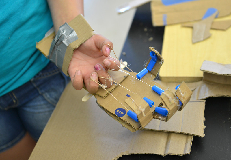 Justin Sheely | The Sheridan Press<br /> A student shows off her cardboard hand during the Summer STEM Camp at Sheridan Junior High School Thursday, June 14, 2018. The STEM camp focused on biomedical engineering this year and students performed cow eyeball surgery, created and programmed robotic hands and made prosthetic legs.