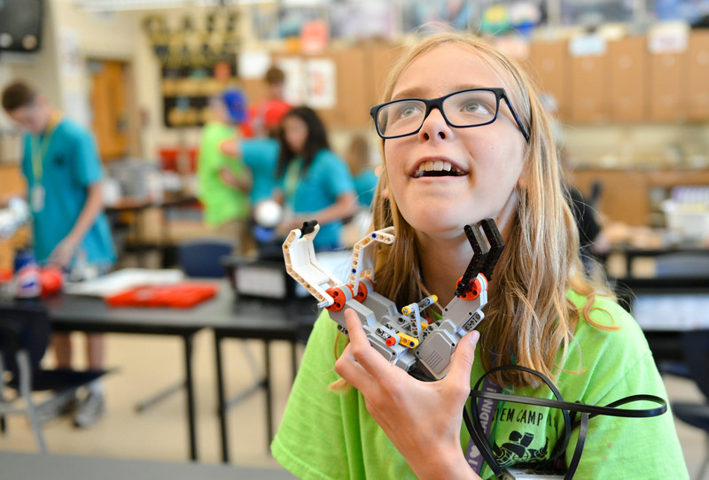 Justin Sheely | The Sheridan Press<br /> Sixth-grader Katelyn Crump plays with her robotic hand during the Summer STEM Camp at Sheridan Junior High School Thursday, June 14, 2018. The STEM camp focused on biomedical engineering this year and students performed cow eyeball surgery, created and programmed robotic hands and made prosthetic legs.