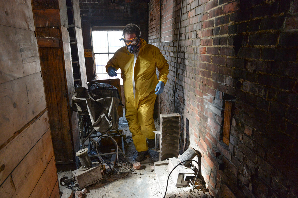 Justin Sheely | The Sheridan Press<br /> Kim Ostermyer steps past equipment left in the hall of the attic of the old Sheridan Iron Works Building on Friday, May 26, 2017. Ostermyer, manager of the Wyoming Room in the Sheridan County Fulmer Public Library, is saving the logs, drawings, invoices and other records that has been kept in the attic of the brick building for more than 100 years. The work is slow, messy and hazardous due to the conditions of the attic, which contains decades of dust, water leaks, and dead birds. Ostermyer wears special equipment as precautions against any health risks. He says that the collection is valuable since the Sheridan Iron Works is one of the last of the oldest businesses in Sheridan to shut down. The record keeping the business had over the years was meticulous and stored over the years – a gold mine for any local historian.