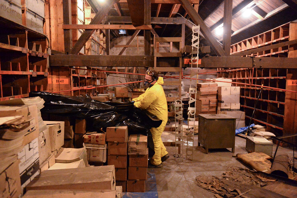 Justin Sheely | The Sheridan Press<br /> Kim Ostermyer pulls a tarp from a pile of boxes he has collected over the past weeks in the attic of the old Sheridan Iron Works Building on Friday, May 26, 2017. Ostermyer, manager of the Wyoming Room in the Sheridan County Fulmer Public Library, is saving the logs, drawings, invoices and other records that has been kept in the attic of the brick building for more than 100 years. The work is slow, messy and hazardous due to the conditions of the attic, which contains decades of dust, water leaks, and dead birds. Ostermyer wears special equipment as precautions against any health risks. He says that the collection is valuable since the Sheridan Iron Works is one of the last of the oldest businesses in Sheridan to shut down. The record keeping the business had over the years was meticulous and stored over the years – a gold mine for any local historian.
