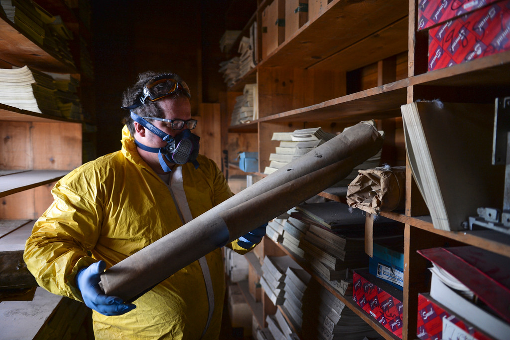 Justin Sheely | The Sheridan Press<br /> Kim Ostermyer pulls drawings from a shelf in the attic of the old Sheridan Iron Works Building on Friday, May 26, 2017. The shelves sit in front of an open window, exposed to the elements and birds. Ostermyer, manager of the Wyoming Room in the Sheridan County Fulmer Public Library, is saving the logs, drawings, invoices and other records that has been kept in the attic of the brick building for more than 100 years. The work is slow, messy and hazardous due to the conditions of the attic, which contains decades of dust, water leaks, and dead birds. Ostermyer wears special equipment as precautions against any health risks. He says that the collection is valuable since the Sheridan Iron Works is one of the last of the oldest businesses in Sheridan to shut down. The record keeping the business had over the years was meticulous and stored over the years – a gold mine for any local historian.
