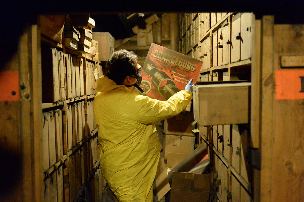 Justin Sheely | The Sheridan Press<br /> Kim Ostermyer explores one of the aisles of records in the attic of the old Sheridan Iron Works Building on Friday, May 26, 2017. Ostermyer, manager of the Wyoming Room in the Sheridan County Fulmer Public Library, is saving the logs, drawings, invoices and other records that has been kept in the attic of the brick building for more than 100 years. The work is slow, messy and hazardous due to the conditions of the attic, which contains decades of dust, water leaks, and dead birds. Ostermyer wears special equipment as precautions against any health risks. He says that the collection is valuable since the Sheridan Iron Works is one of the last of the oldest businesses in Sheridan to shut down. The record keeping the business had over the years was meticulous and stored over the years – a gold mine for any local historian.