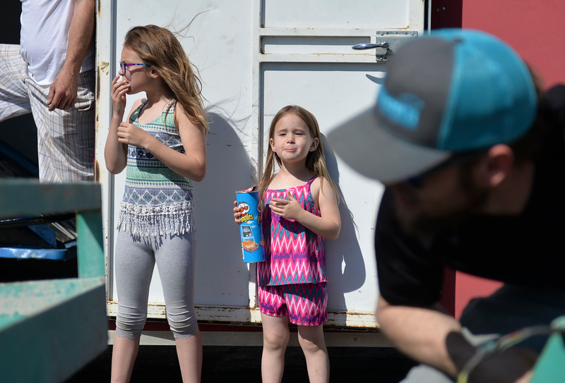 Justin Sheely | The Sheridan Press<br /> Nine-year-old Brynlee Fischer, left, and Isabell Schwarzbach, 4, look on as Joe Fischer cranks the trailer lift to unload a dirt racing car during the Sheridan Motorsports Association Car Show at the Holiday Inn Saturday, April 28, 2018.
