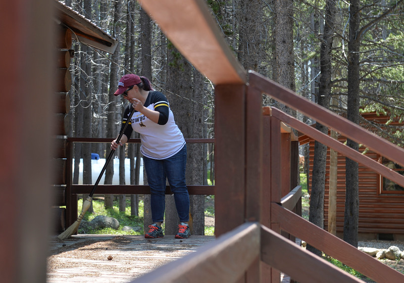 Justin Sheely | The Sheridan Press<br /> NWCCD employee Allyssa Torres sweeps the deck of a cabin at Spear-O Wigwam in the Bighorn National Forest Thursday, June 28, 2018. The NWCCD board approved the potential sale on June 20 of Spear-O Wigwam, a 67,850-acre area in the Bighorn Mountains. The college leased the property since 2011 and used it for summer education programs and performances.