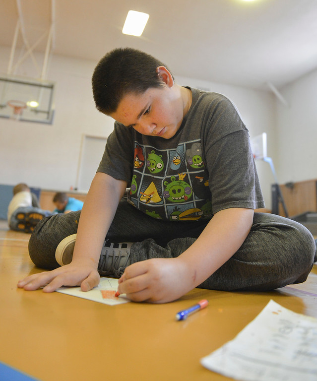 Justin Sheely | The Sheridan Press<br /> Fifth-grader Ryan Alberding draws a paper boomerang at Arvada-Clearmont school Wednesday, May 2, 2018. Australian-American educator, artist and ambassador Paul Taylor visited Clearmont for two days last week to talk about aboriginal culture and teach students how to make a didgeridoo and boomerang.