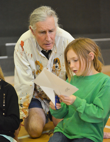 Justin Sheely | The Sheridan Press<br /> Australia native Paul Taylor looks on as first-grader Jessi Holland cuts out a paper boomerang at Arvada-Clearmont school Wednesday, May 2, 2018. Australian-American educator, artist and ambassador Paul Taylor visited Clearmont for two days last week to talk about aboriginal culture and teach students how to make a didgeridoo and boomerang.
