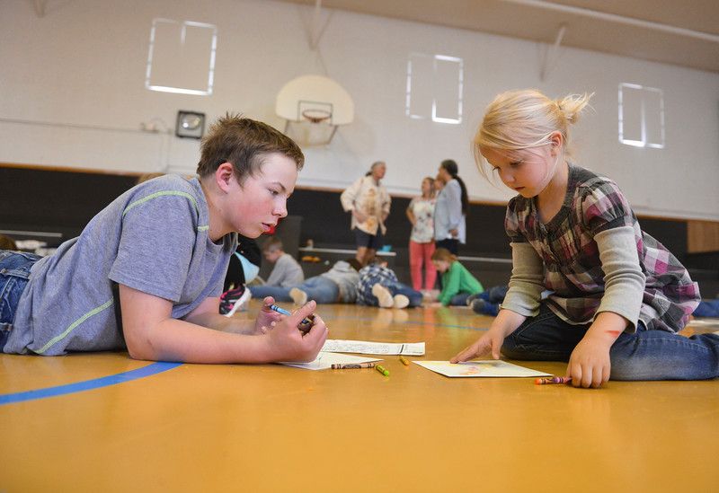Justin Sheely | The Sheridan Press<br /> Sixth-grader Miles Packard, left, helps kindergartener Aurora Makela draw a paper boomerang at Arvada-Clearmont school Wednesday, May 2, 2018. Australian-American educator, artist and ambassador Paul Taylor visited Clearmont for two days last week to talk about aboriginal culture and teach students how to make a didgeridoo and boomerang.