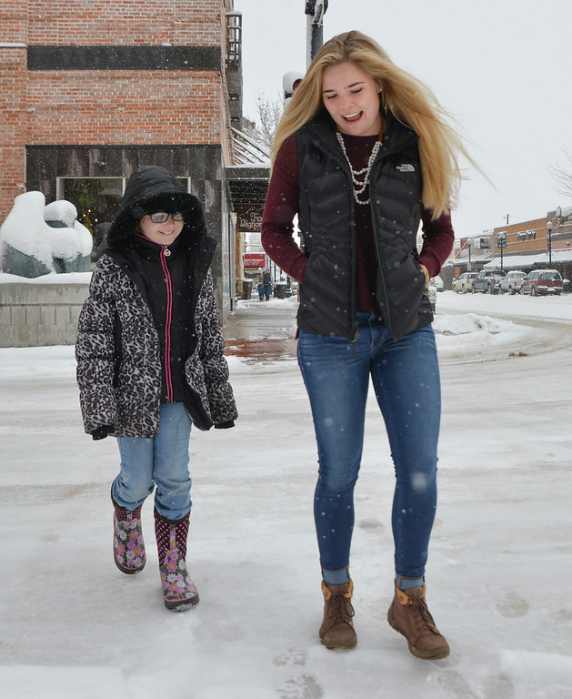 Justin Sheely | The Sheridan Press<br /> Katelynn Brooks, right, walks with her little Chloe Granum,10, along Main Street Saturday, March 31, 2018. The Brooks siblings are described as people with happy hearts who give back to the community through volunteering.