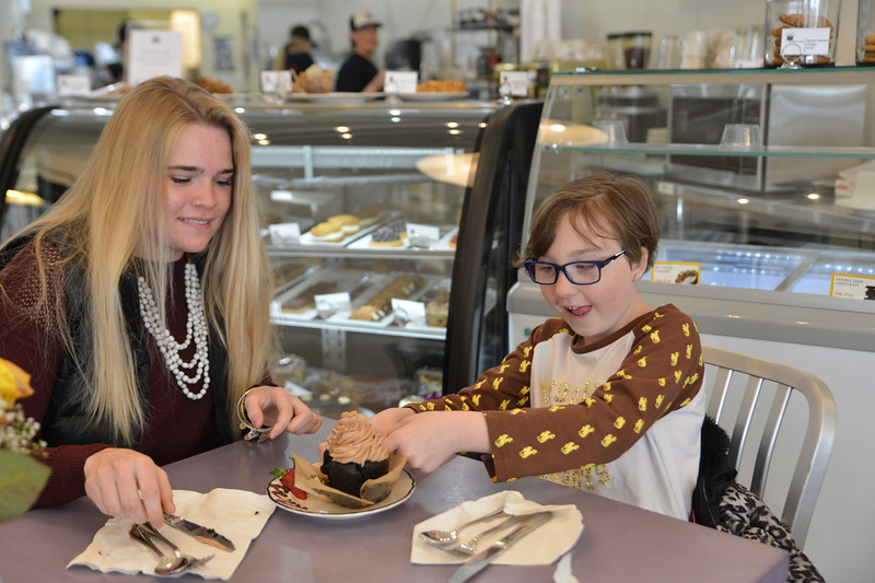 Justin Sheely | The Sheridan Press<br /> Katelynn Brooks, left, shares a chocolate cupcake with her little Chloe Granum,10, at Red Velvet Saturday, March 31, 2018. The Brooks siblings are described as people with happy hearts who give back to the community through volunteering.