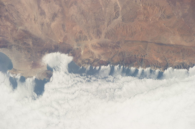 WEATHER CHANNEL: This image illustrates off-shore flow along the coast of Chile. Cool, drier air moving off of the Chilean landmass and over the Pacific Ocean warms and absorbs water vapor from the ocean. The air is now buoyant, and as it rises over the Pacific, the air cools again, and the water vapor condenses into a thick cloud bank.