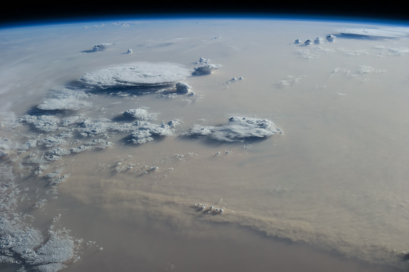 WEATHER CHANNEL: In this image, an immense dust storm is captured by an ISS astronaut. A few cumulonimbus clouds break through the thick lower level clouds.