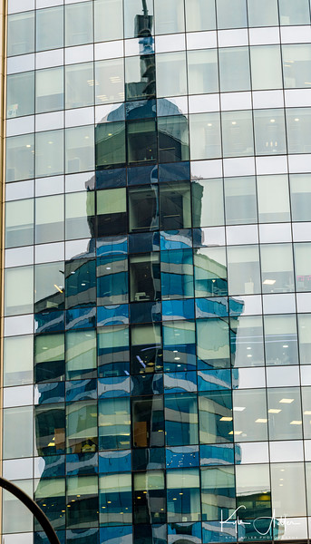 Santiago Cathedral's tower reflected in the windows of a modern glass office building.